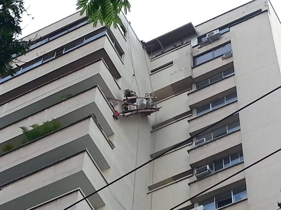 Bomberos de Cali socorren dos trabajadores que cuelgan de un edifico en la avenida Sexta